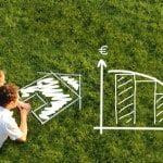 Pärchen in Wiese vor Haus planen Baufinanzierung